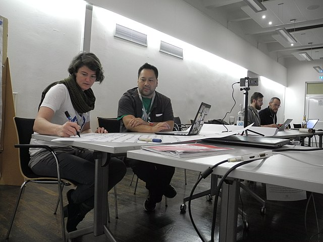 Two participants next to each other and communicating; one on a computer, the other with a sheet of paper, writing notes.